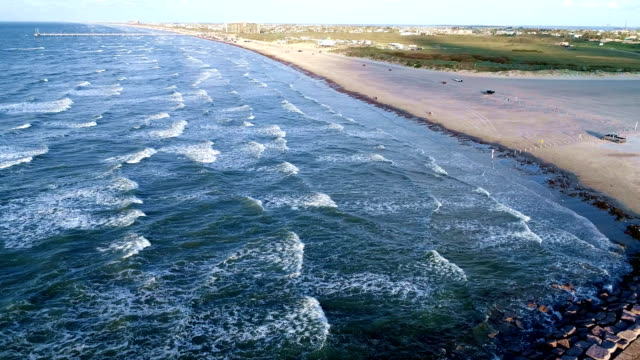 waves crashing in cove around beach and jetti on paradise destination texas gulf coast beach port aransas - corpus christi texas stock videos & royalty-free footage