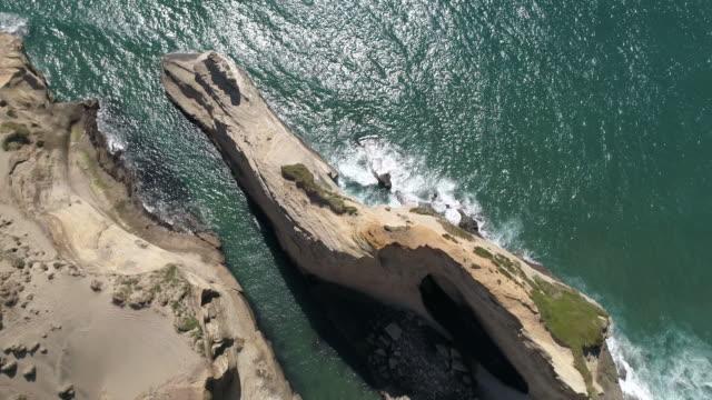 Waves crashing into sandstone cliffs