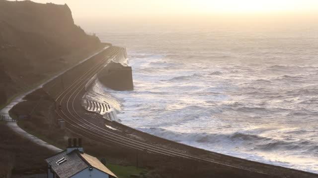 Waves crashing off the sea wall protecting the rai