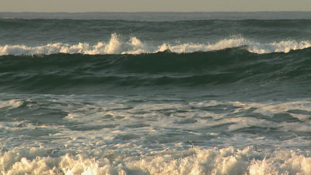 waves crashing on beach at sunrise - rolling stock videos & royalty-free footage