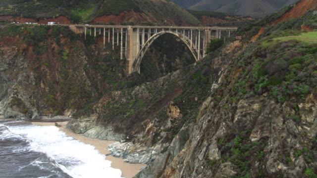 waves crashing on beach beneath bixby creek bridge - bixby creek bridge stock videos & royalty-free footage