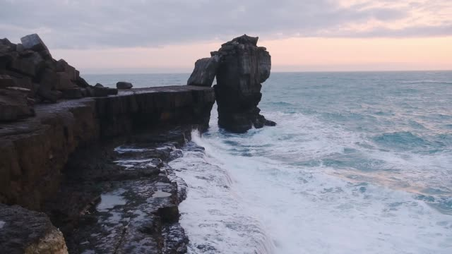 waves crashing on pulpit rock, portland, england, on a cloudy evening - extreme terrain stock videos & royalty-free footage
