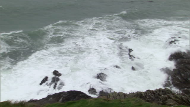 ws pan waves crashing on rocks / county cork, munster, ireland - county cork stock videos & royalty-free footage