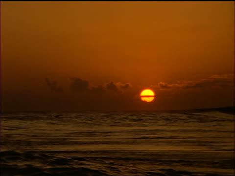 Waves crashing on rough seas at sunset / Maldives Islands, Indian Ocean