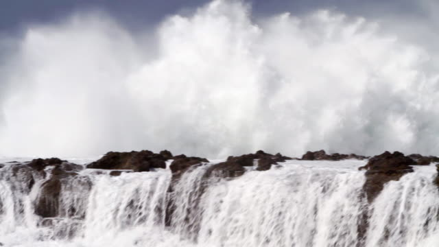 ms pan waves crashing shore on lava rocks   / haleiwa, hawaii, united states - rock type stock videos and b-roll footage