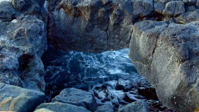 waves crashing through cave close  kauai hawaii - polynesia stock videos & royalty-free footage