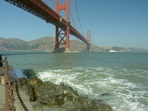 vídeos de stock, filmes e b-roll de ws waves crashing under golden gate bridge at fort point / usa  - menos de 10 segundos