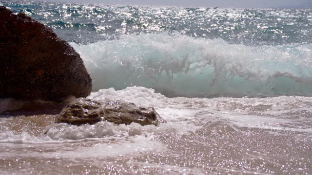 vídeos de stock, filmes e b-roll de slo mo ondas da repressão contra rock na praia - raw footage