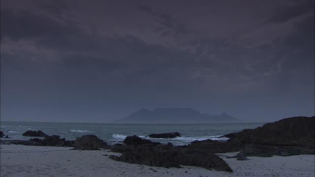 waves flow onto a rocky shore. - 南ア テーブルマウンテン点の映像素材/bロール