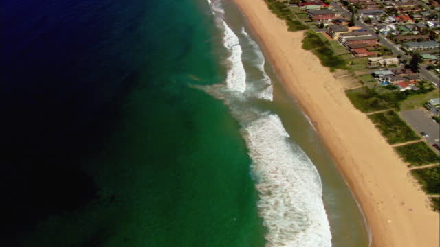 WS AERIAL Waves from green water crashing onto Sydney beach, houses and buildings visible near shoreline, Sydney, New South Wales, Australia