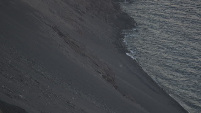 Waves gently lap the edge of the island of Stromboli which sits in the Tyrrhenian Sea, Italy.
