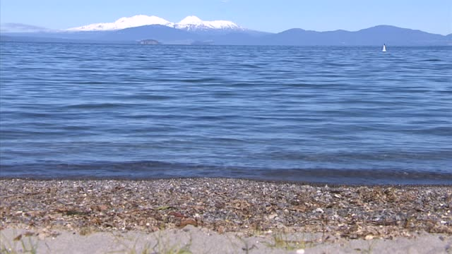 Waves gently lapping at shore of Lake Taupo with snow capped mountains visible across water