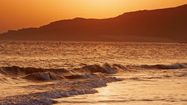 vídeos de stock e filmes b-roll de waves gently washing the sandy beach at sunset - cena de tranquilidade