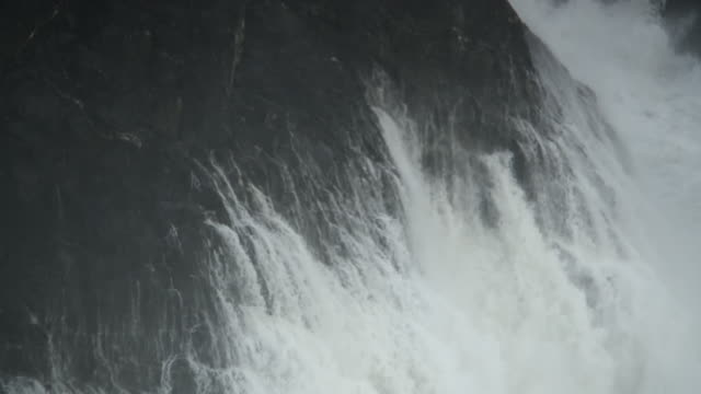 vídeos de stock, filmes e b-roll de waves hitting cliff in slow motion - erodido