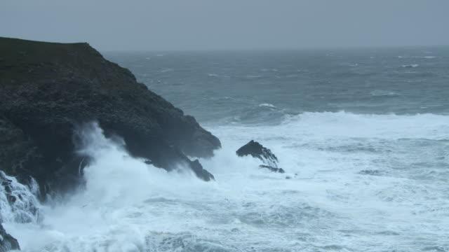 vídeos de stock, filmes e b-roll de waves hitting headland in cornwall - pedra rocha
