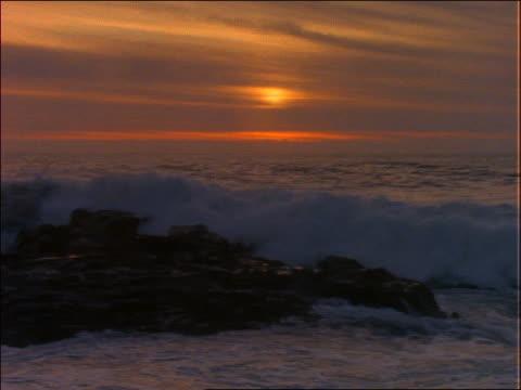 vídeos de stock, filmes e b-roll de waves hitting rocks in ocean at sunset - céu romântico