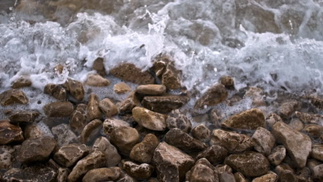 waves hitting stones on the beach - hitting stock videos and b-roll footage