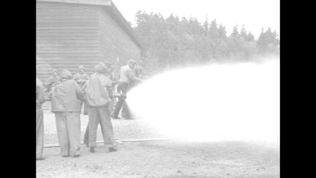 waves in firefighting suits shooting water from hose into hatch on top of building that smoke is coming out of / waves shooting water from hose into... - fire hose stock videos & royalty-free footage