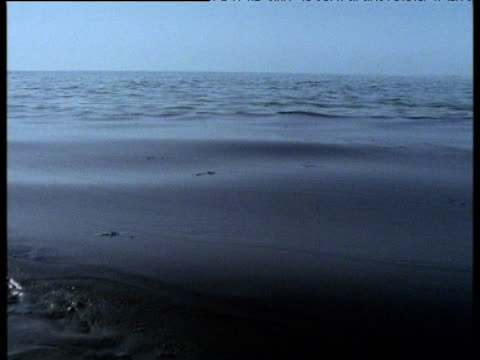 waves lap on shore, thick with black oil slick, saudi arabia, 1991 - persian gulf stock videos & royalty-free footage