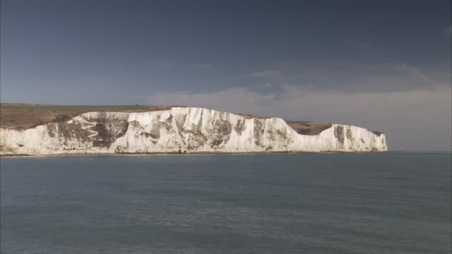 waves lap towards the coast of the white cliffs of dover. - dover kent stock-videos und b-roll-filmmaterial