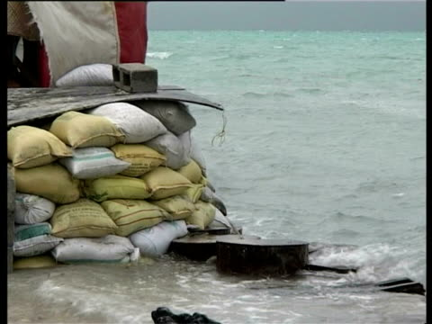 waves lapping against sand bags, kiribati, central pacific - sandbag stock videos and b-roll footage