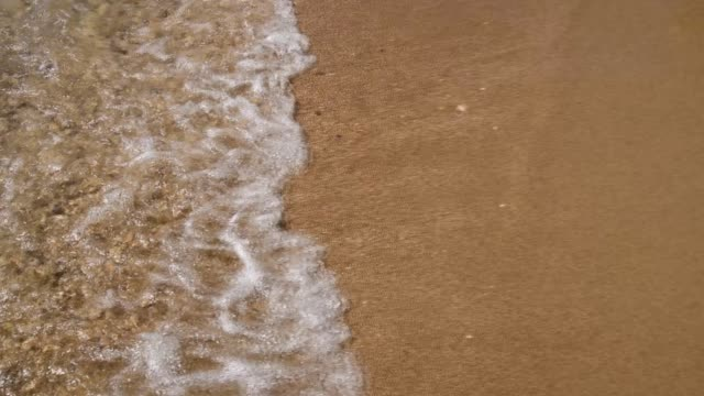 waves lapping on the sandy shore. - foam stock videos & royalty-free footage