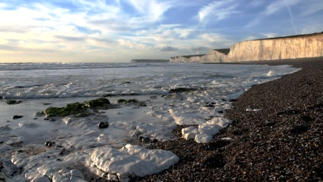 waves lapping the shoreline, seven sisters chalk cliffs, east sussex, uk - east sussex stock videos & royalty-free footage