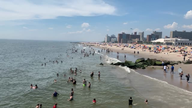 stockvideo's en b-roll-footage met waves move back and forth as people wade in the water at the beach at coney island on july 19, 2020 in the brooklyn borough of new york city. much of... - zwembroek