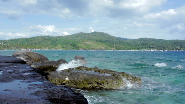 waves of water splashing on big rocks with mountain on background - batangas province stock videos and b-roll footage