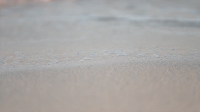 CU, SELECTIVE FOCUS Waves on a sandy beach / Ibiza, Spain