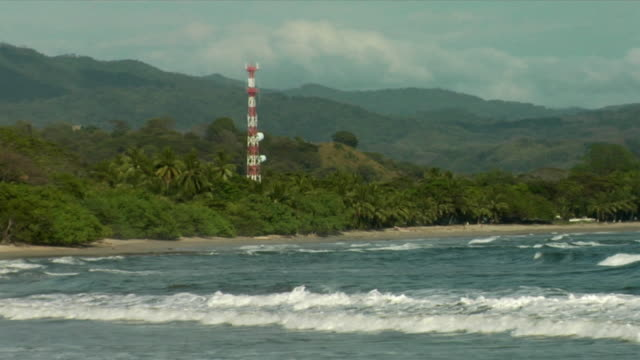 ws, waves on beach and green hill with mobile phone mast, nosara, guanacaste, costa rica - nosara stock videos and b-roll footage
