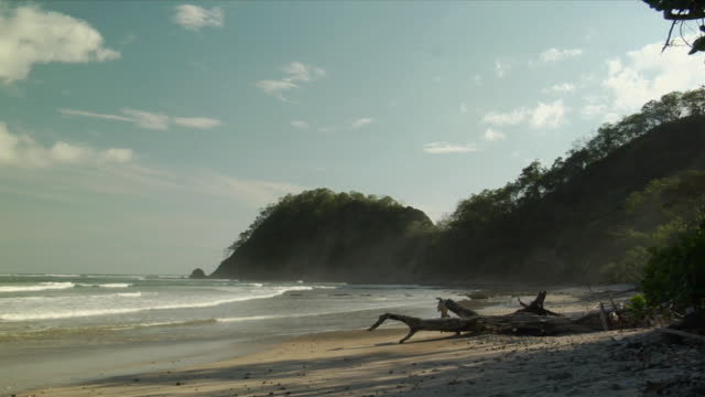 ws, waves on beach and green hills, nosara, guanacaste, costa rica - nosara stock videos and b-roll footage