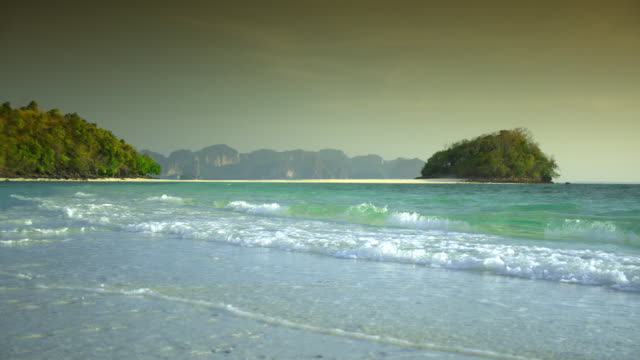 ms pan waves on beach and tropical island, krabi, thailand - see other clips from this shoot 1459 stock videos and b-roll footage