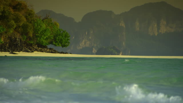 cu waves on beach, cliffs in background, krabi, thailand - see other clips from this shoot 1459 stock videos and b-roll footage