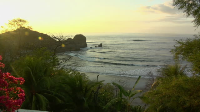 ws, waves on beach seen from green hill at sunset, nosara, guanacaste, costa rica - nosara stock videos and b-roll footage