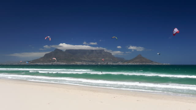 t/l waves on blouberg beach, kitesurfers over sea, cape town in background, south africa - kiteboarding stock videos & royalty-free footage