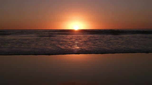 vidéos et rushes de ws waves on piha beach at sunset, auckland, new zealand - coucher de soleil