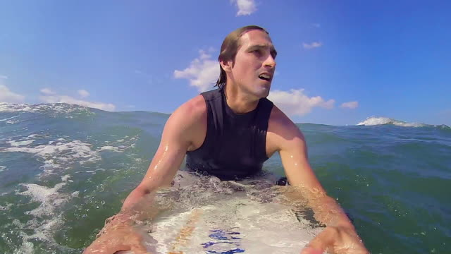 pov: waves pass by a surfer paddling - oar stock videos & royalty-free footage