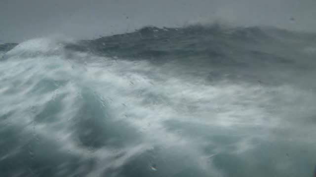 waves rage in a stormy ocean. available in hd. - roh stock-videos und b-roll-filmmaterial