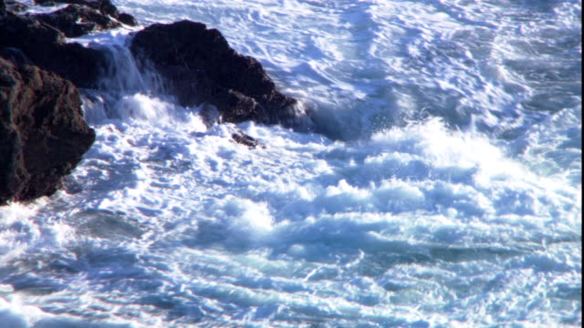 waves roil against boulders on the coast of a channel island. - kanalinseln stock-videos und b-roll-filmmaterial