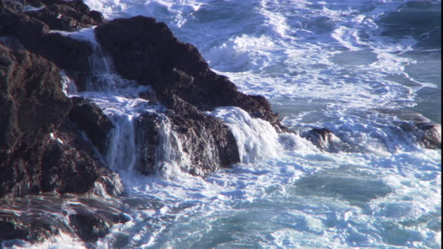 waves roil against boulders on the coast of a channel island. - boulder stock videos & royalty-free footage