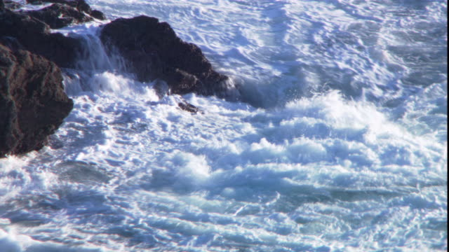 waves roil against boulders on the coast of a channel island. - 英国海峡 チャンネル諸島点の映像素材/bロール