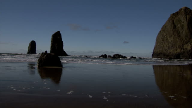 waves roll around rock formations near haystack rock at cannon beach on the oregon coast. available in hd. - oregon coast stock videos & royalty-free footage
