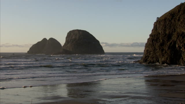 waves roll gently onto a peaceful beach off the oregon coast. available in hd. - oregon coast stock videos and b-roll footage