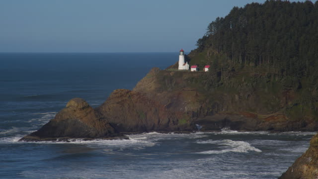 waves roll in around the heceta head lighthouse in oregon. - heceta head stock videos & royalty-free footage