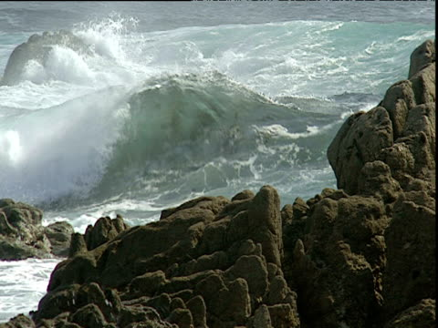 Waves roll in towards shore and break over rocky foreground Spain