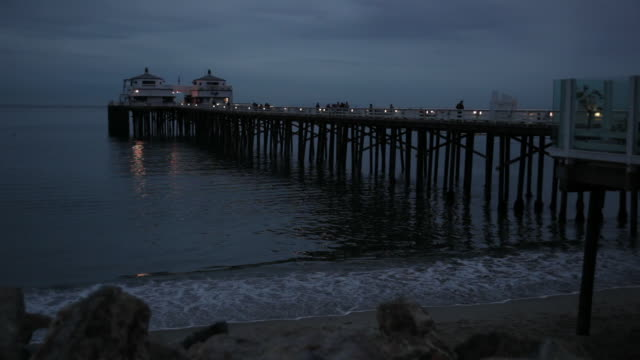 ws waves roll in under a pier in malibu / california - malibu stock videos & royalty-free footage