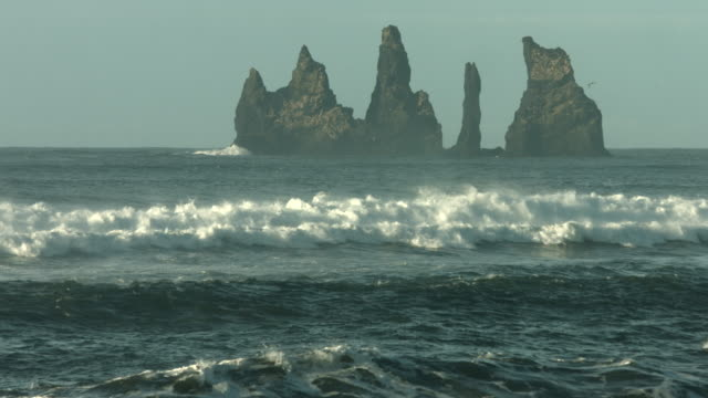 Waves roll onto a beach near the Reynisdrangar sea stacks in southern Iceland.