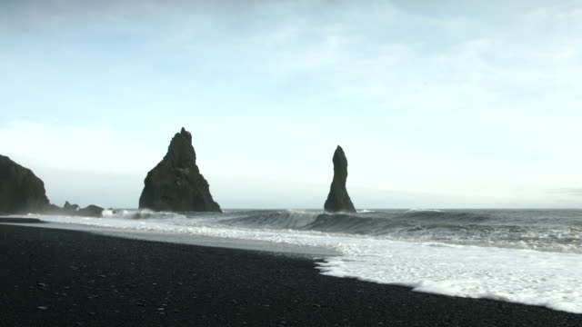 Waves roll onto a beach near the Reynisdrangar sea stacks in southern Iceland.