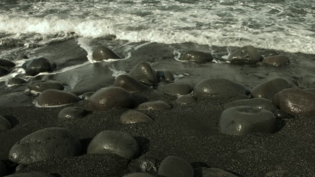 Waves roll onto a pebble beach in Iceland.